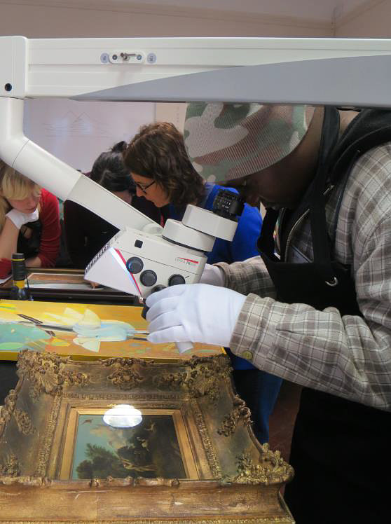 Click the image for a view of: Barnabas using the stereo microscope to examine a Bailey painting